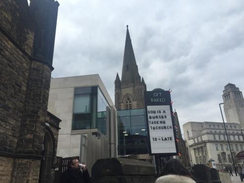 Cartel frente a una antigua iglesia: 'God is a burguer'.